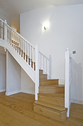 Interior stairway with a glass railing.
